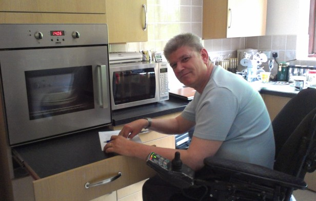 Wheelchair user in his accessible kitchen